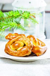 Christmas pretzel under fir branch. White candle in iron lantern